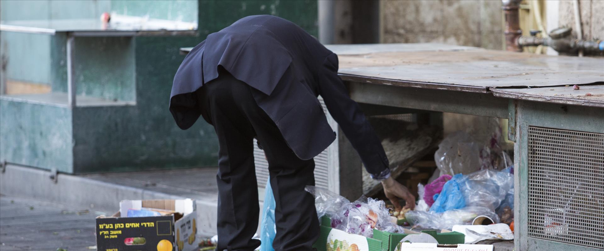 אדם מחטט באשפה בשוק מחנה יהודה בירושלים