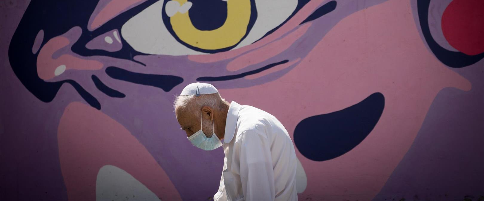 אדם עם מסיכה הולך ליד קיר גרפיטי בימי קורונה, ירוש