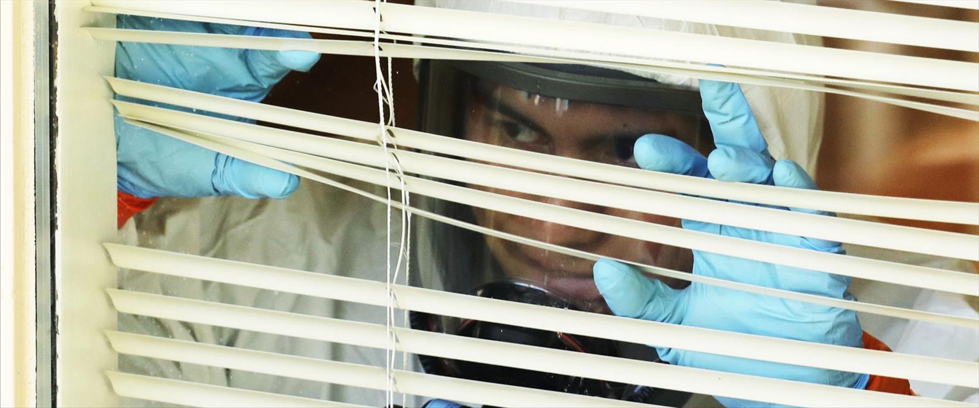 עובד בצוות התאוששות לבוש בחליפת מגן במרכז רפואי בק
