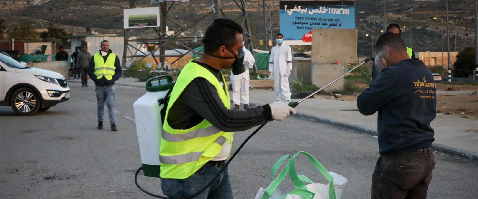 פועל פלסטיני עובר חיטוי בשובו מישראל, בכניסה לכפר