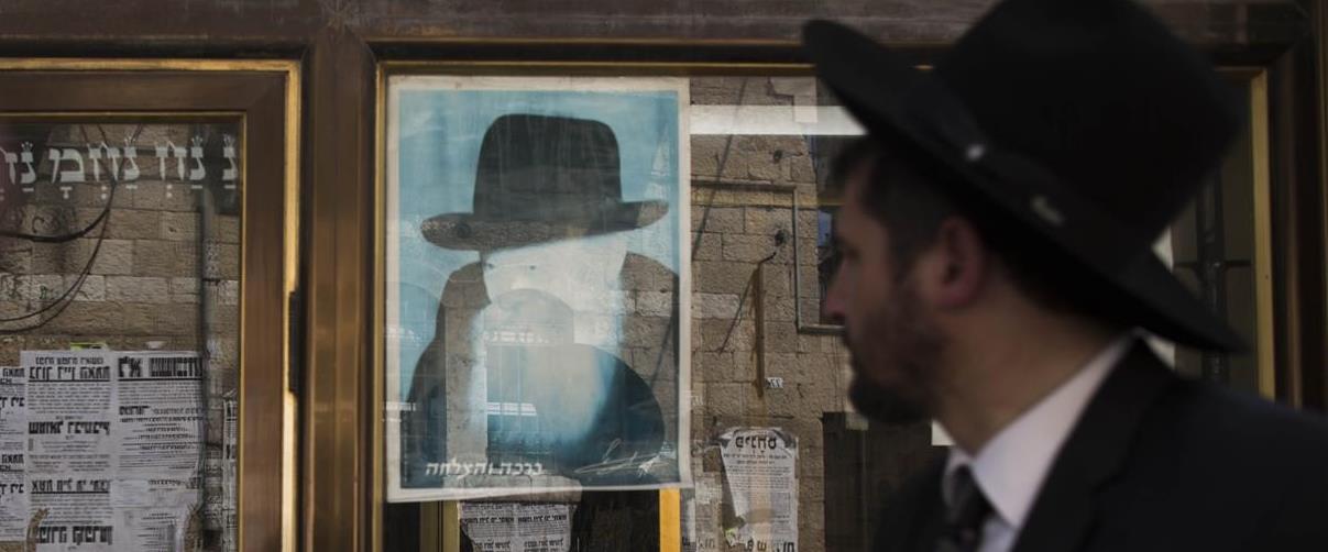 צעיר חרדי מתבונן בתמונת הרבי מליובאוויטש