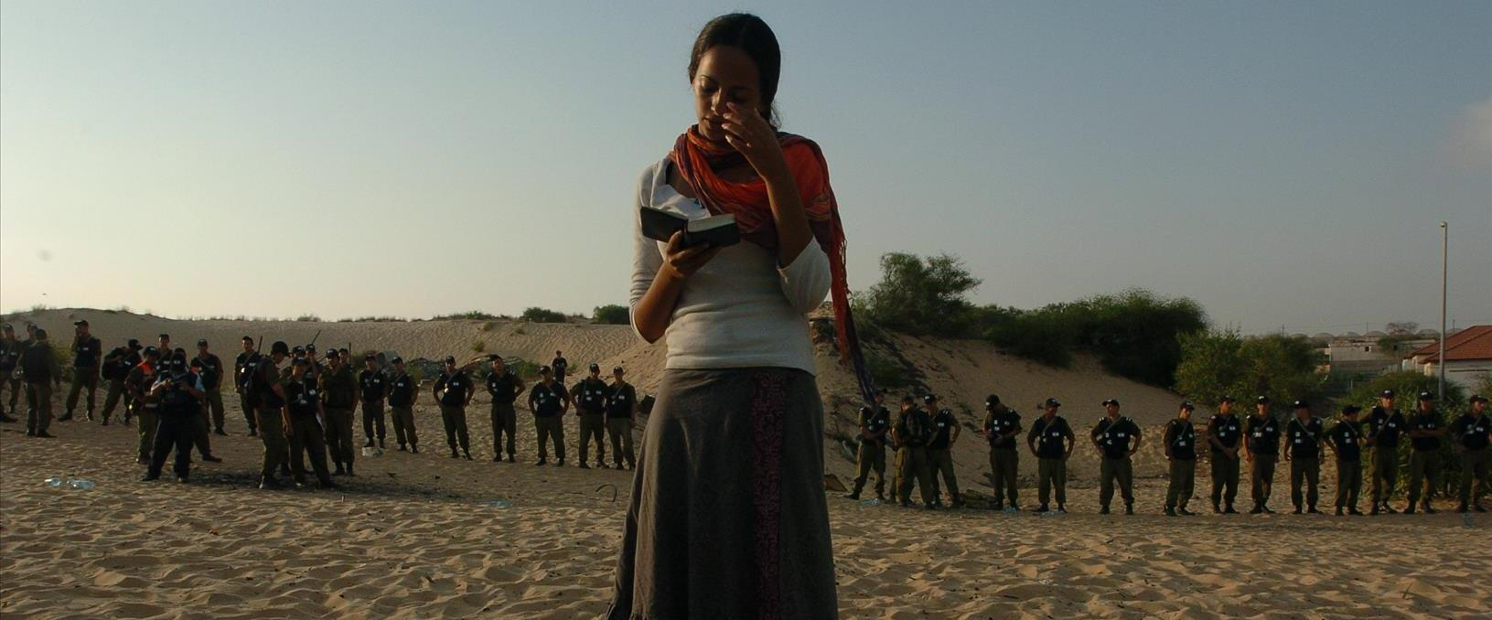 נערה מתפללת בעת פינוי בית הכנסת בנווה דקלים