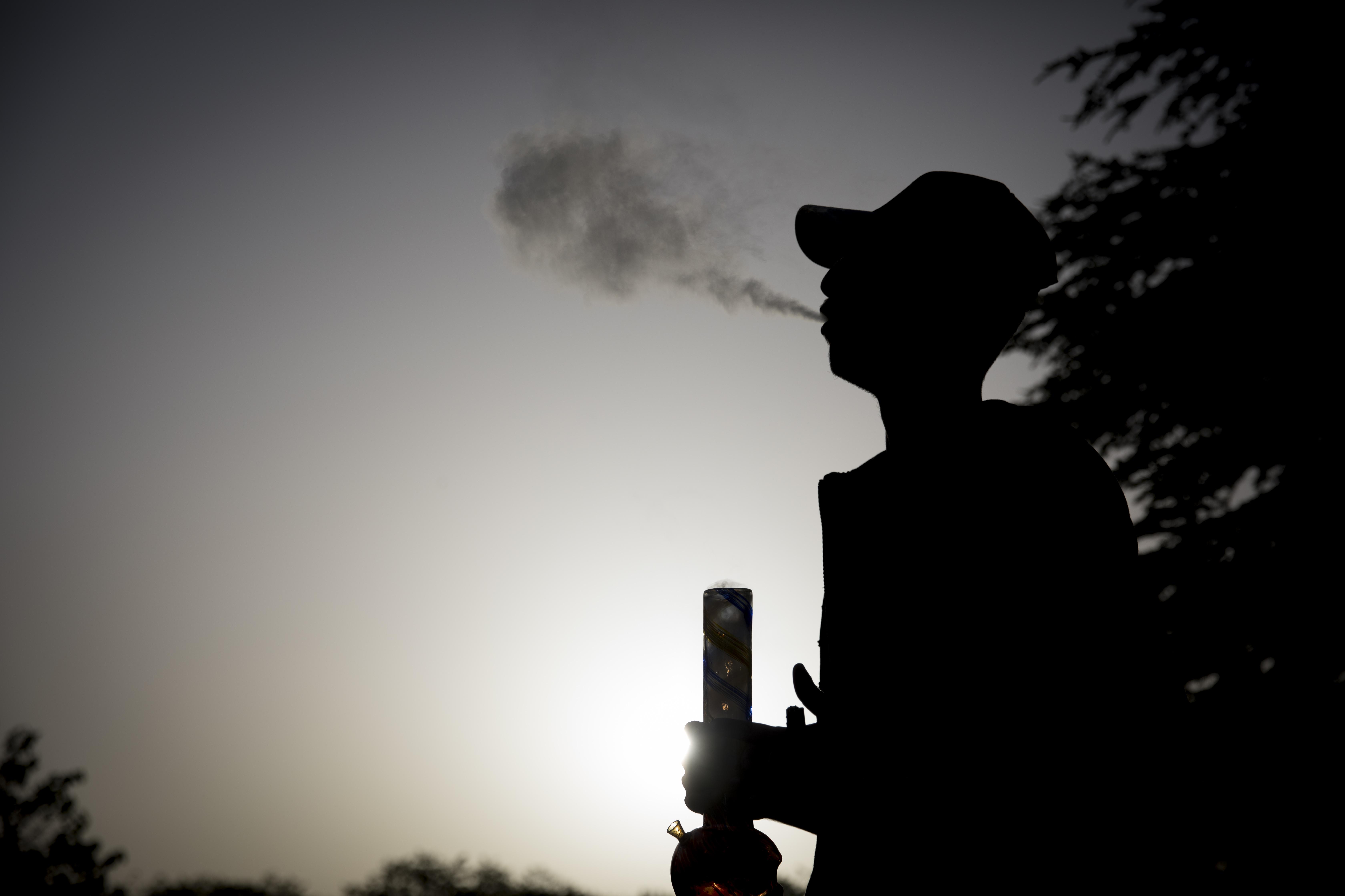אדם מעשן באנג בהפגנה למען לגליזציה מול הכנסת באפריל 2017 (יונתן זינדל, פלאש 90)