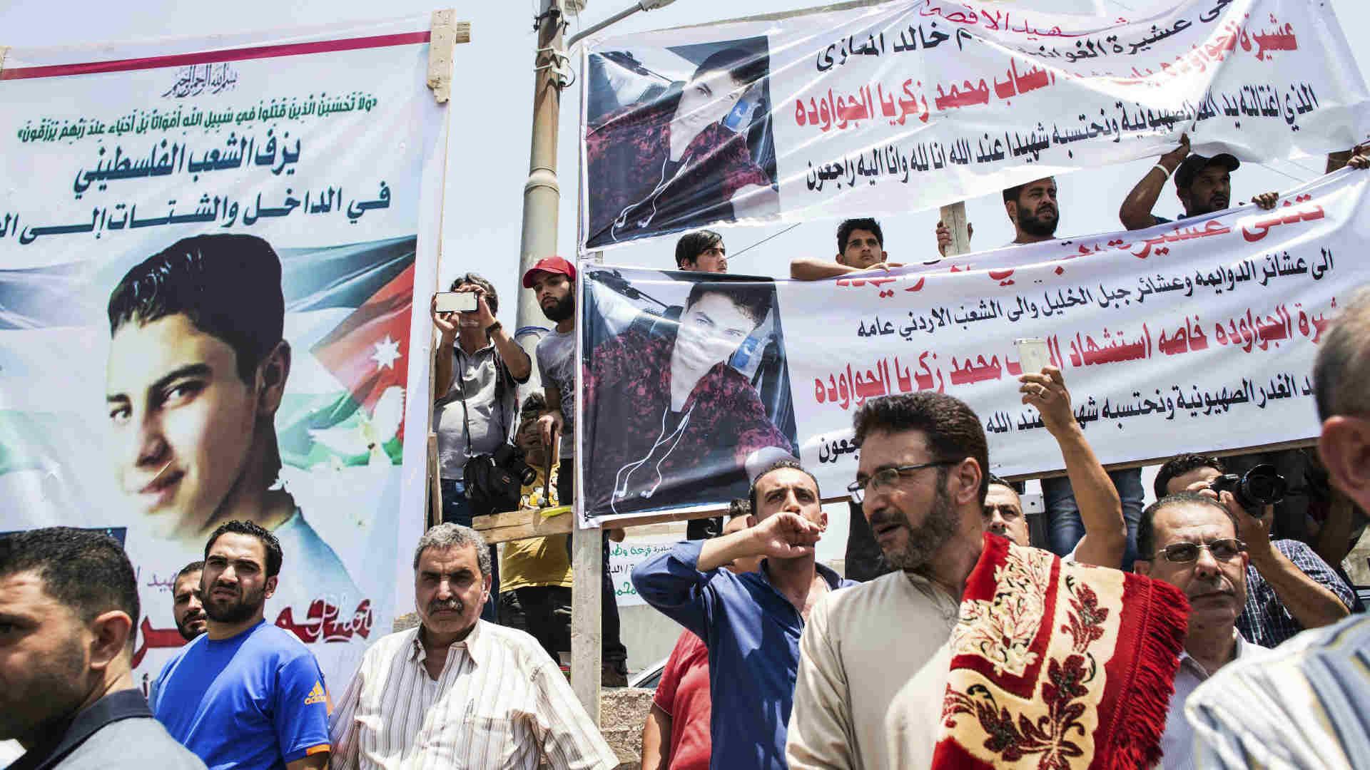 מפגינים בעמאן עם תמונותיו של הנער שנהרג בשגרירות