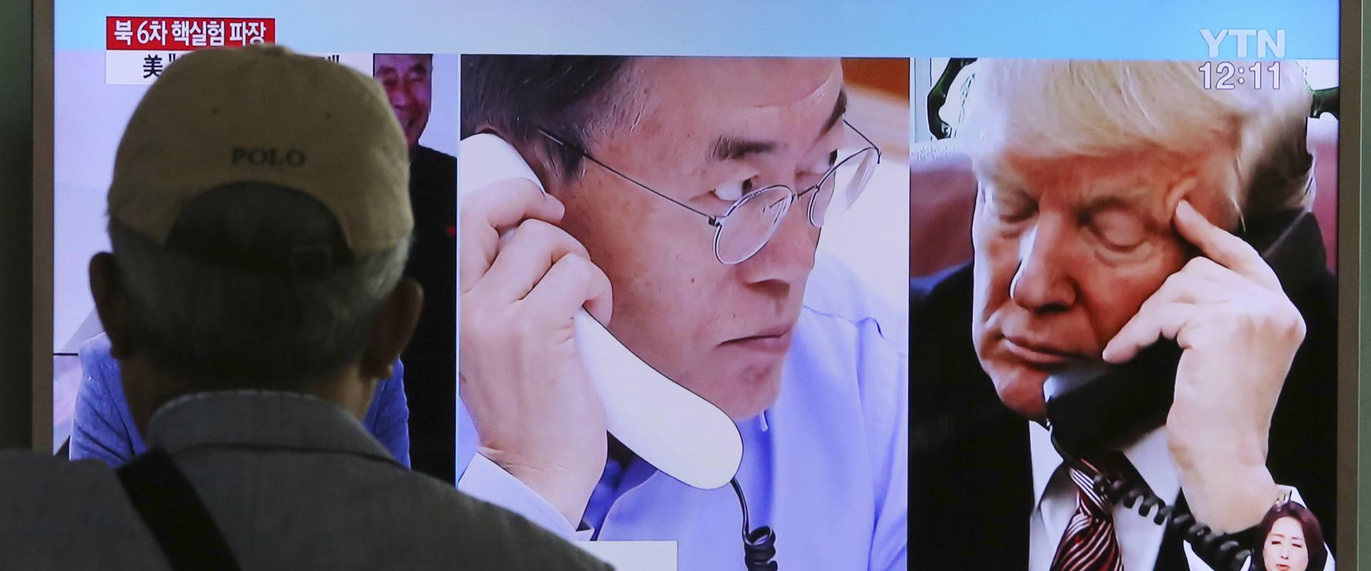 """אדם בסיאול צופה בשידור בו נראים נשיאי ארה""""ב וקוריא"""