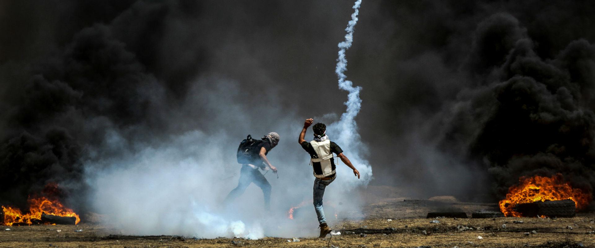 פלסטינים מפגינים ליד גדר המערכת בעזה, בשבוע שעבר